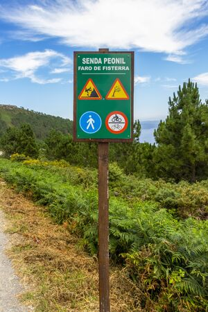 Pedestrian path Faro de Fisterra sign from the Fisterra lighthouse or Cape Finisterre to Fisterra in Galicia, Spain 免版税图像