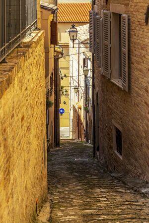 View of a beautiful narrow steep street in Fermo, Province of Fermo, Marche Region, Italy 免版税图像