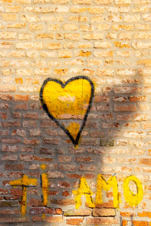FERRARA, ITALY - MAY 28, 2018: A heart and the words Ti Amo, or I love you in English painted with yellow paint on an old brick wall, street art in Ferrara, Emilia-Romagna, Italy Sajtókép