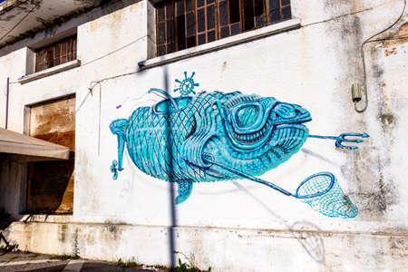 PORTO LAGOS, GREECE - NOVEMBER 30, 2019: Surreal artwork on an abandoned building wall at Porto Lagos Port 新闻类图片