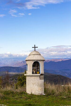 Shrine or kandilakia of St. Athanasius on a blurred mountain background at Nestos Gorge Observatory in Topeiros Municipality, Xanthi Region, Greece. Translation - St. Athanasius