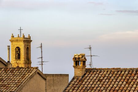 Typical building rooftop with a chimney in Recanati, Province of Macerata, Marche Region, Italy, the blurred bell tower of the Church and Convent of San Francesco in the background 免版税图像