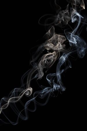 Two delicate columns of smoke from incense stick isolated on black background, selective focus