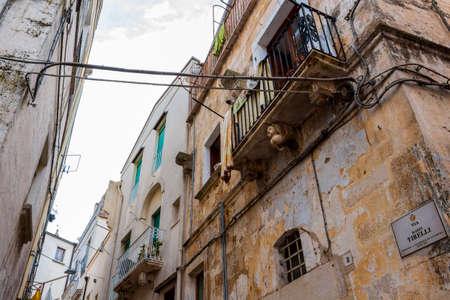 ALTAMURA, ITALY - AUGUST 26, 2018: Old town street view in Altamura, Apulia, Italy. Via Mario Tirelli or Mario Tirelli Street partial low-angle high section view with decoration 新闻类图片