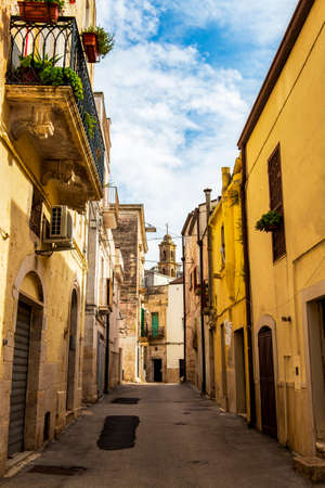ALTAMURA, ITALY - AUGUST 26, 2018: Old town street view with a church bell tower in the background in Altamura, Apulia, Italy
