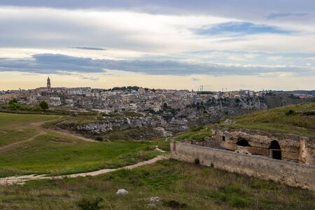 Parco della Murgia Materana or Park of the Rupestrian Churches of Matera with ancient architecture, distant panoramic view of Matera in the backgrond. Province of Matera, Basilicata Region, Italy at sunset 免版税图像