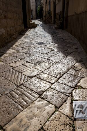 Old town street pavement contre-jour view in Altamura, Apulia, Italy