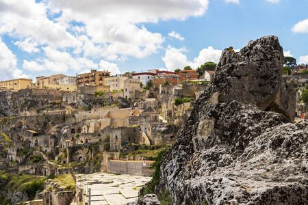Blurred old town sunny summer cityscape behind ancient rock in Matera, Province of Matera, Basilicata Region, Italy