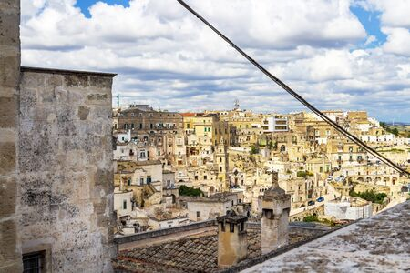 Matera old town cityscape behind a chimney with famous chimney cap, beautiful chimney decoration on a rooftop in Matera, Province of Matera, Basilicata Region, Italy 免版税图像