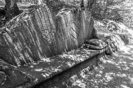 BOMARZO, ITALY - JUNE 02 2018: Ancient stone bench in Sacro Bosco, Parco dei Mostri or Park of the Monsters in Bomarzo, Province of Viterbo, Lazio, Italy, black and white photography