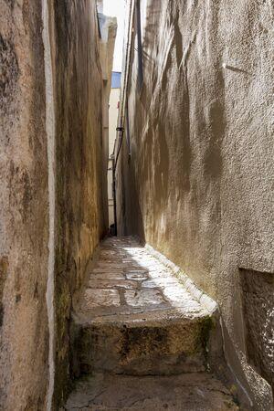 Old town narrow pedestrian walkway between street building walls in Altamura, Apulia, Italy