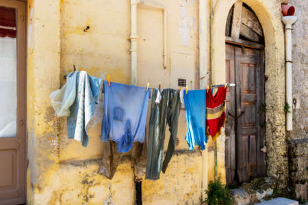 Old battered clothes hanging in the street against old weathered building wall in Matera, Province of Matera, Basilicata Region, Italy 免版税图像
