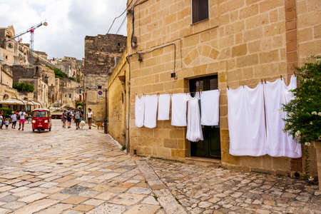 MATERA - ITALY - AUGUST 27, 2018: White laundry hanging in the street in Matera, Province of Matera, Basilicata Region, Italy, blurred touristic street view in the old town 新闻类图片