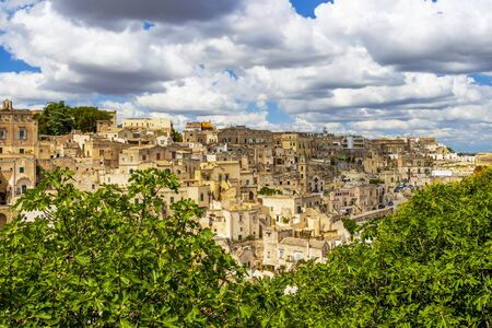 Scenic panoramic sunny view of Matera, Province of Matera, Basilicata Region, Italy behind fig trees under beautiful cloudy summer sky