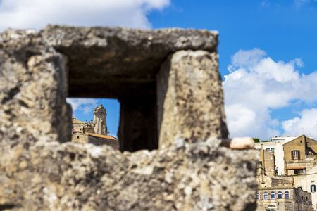 Abstract city view, architectural detail of an old building in the Matera old town as seen through blurred stone fence frame in Matera, Province of Matera, Basilicata Region, Italy