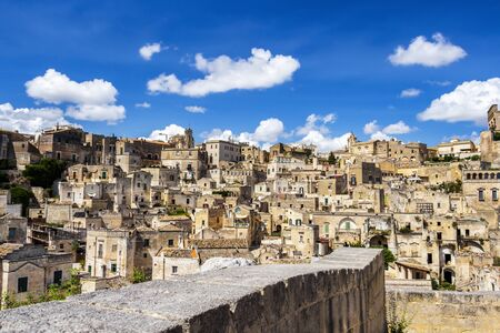 Old town panoramic sunny summer view of Matera, Province of Matera, Basilicata Region, Italy. Blurred stone fence in the foreground