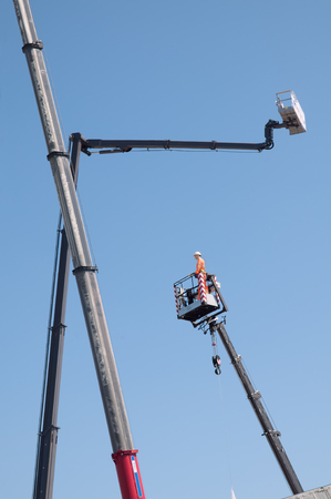 Electrician dummy in basket on cherry picker on blue sky background. Boom and basket of hydraulic telehandler for construction and repair works.