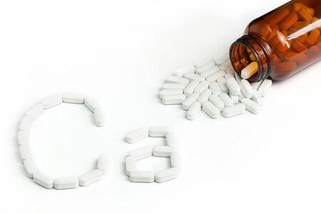 Vista dall'alto di pillole di calcio bianco versando dalla bottiglia di vetro. Compresse Di Integratore Di Calcio Che Formano Ca Forma Su Sfondo Bianco.