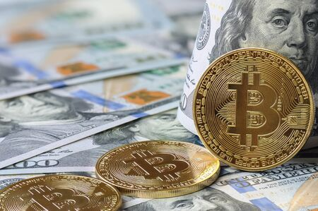 Bitcoin dollar exchange. Golden bitcoin coins (BTC) on background of banknotes US 100 dollars bill with President Benjamin Franklin. Virtual money and digital crypto currency concept.