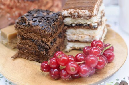 Chocolate cake and red currant on wooden plate with selective focus. Stock Photo