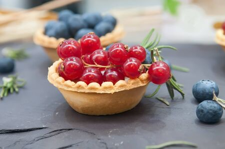 Tartlets with red currant and blueberries. Tartlet with berries on dark background.
