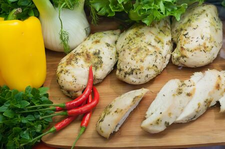 Boiled chicken breast with fresh vegetables and herbs on wooden board on showcase buffet restaurant.