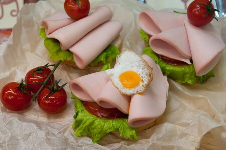 Sandwich with fried eggs, sausage, lettuce and sauce. Fried eggs and sausage sandwich in cafeteria.