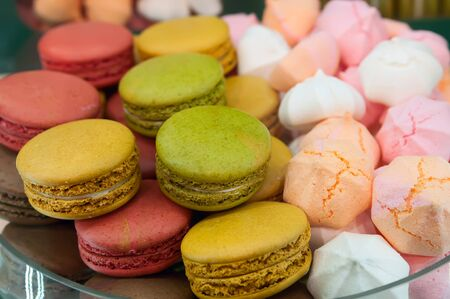 Colorful macaroons and meringue in cafe window. French sweet delicacies.