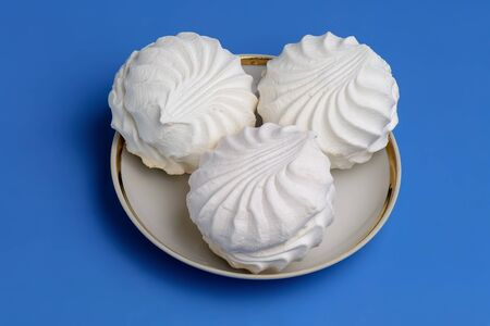 White meringues on plate on blue background. Top view.