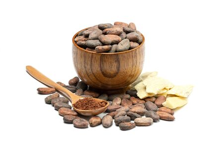 Raw cocoa beans in wooden bowl, cocoa butter and spoon with cocoa powder. Chocolate ingredients isolated on white background. Stock Photo