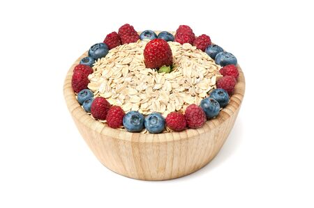 Breakfast cereal with blueberry, raspberry and strawberry in wooden bowl over white background.