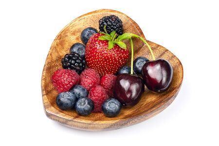 Fresh different berries in wooden bowl in the shape of heart isolated on white background. Full depth of field with clipping path.