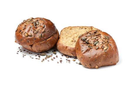 Sliced baked bread rolls with pumpkin seeds and sesame isolated on white background. Half sandwich bun with crisp. Archivio Fotografico
