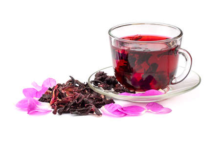 Hibiscus tea in glass cup among the rose petals and dry petals isolated on white background.