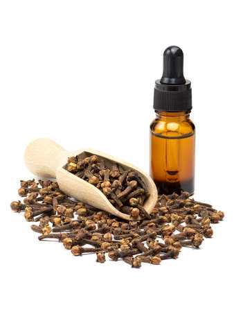 Dried clove spice in the wooden scoop and pure clove essential oil in glass bottle isolated on white background. Full depth of field close-up.