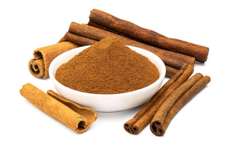 Ground cinnamon in white ceramic bowl and cinnamon sticks isolated on white background. Close-up and full depth of field.