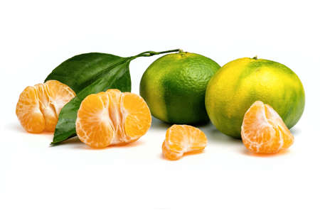 Ripe green and yellow tangerines and orange tangerine slices isolated on white background. Stock Photo