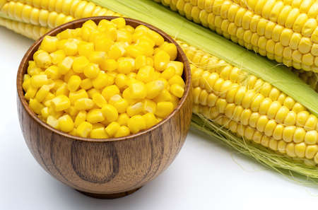 Sweet corn grains in wooden bowl on the background of fresh corn cobs. Fresh sweet corn top view. Stock Photo