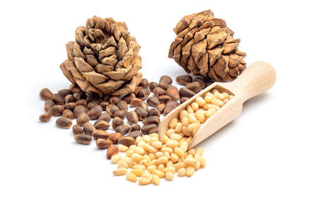 Pine cones and peeled pine nuts in wooden scoop isolated on white background.