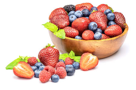 Mixed sweet fresh berries on white background. Ripe strawberry, raspberry, blueberry and mint leaves.
