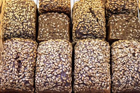 Rye bread with sunflower seeds on shelf in market. Bread background.
