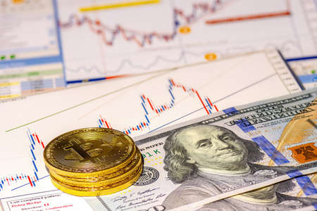 Golden bitcoin coins on financial charts and us dollar background. Concept of cryptocurrency exchange and financial investment.