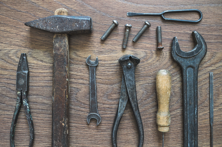 rasp: Different tools (pliers, hammer, awl, wrench, nippers, chisel, rasp, screwdriver) on a wooden background. Stock Photo