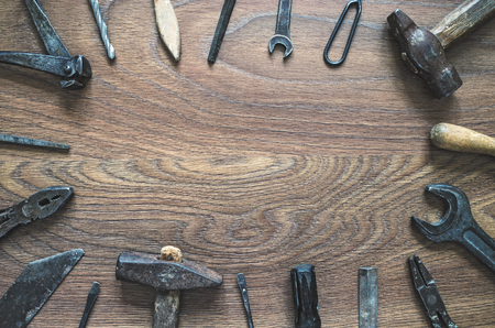rasp: Different tools (pliers, hammer, wrench, nippers, chisel, rasp, screwdriver, drill) on a wooden background. Fathers day card with copy space.