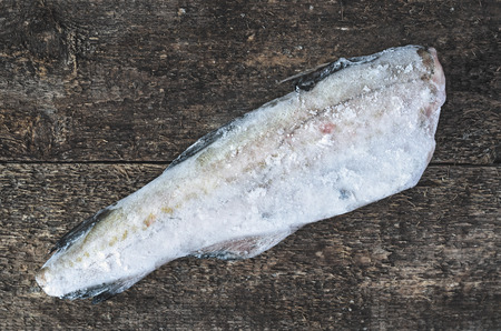 hake: Frozen fish hake on a wooden background Stock Photo