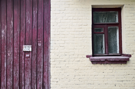 vinous: Old brick yellow wall with window and vinous wooden fence close-up. Stock Photo