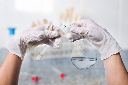 laboratorian: gloved hands holding a glass test tube and flask of clear liquid on a light background research lab, scientist hand during medical test or chemical experience