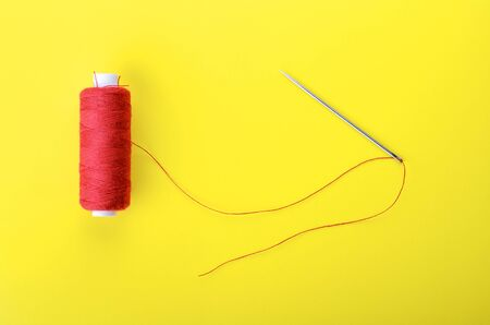 hilo rojo: Spool of red thread and needle on yellow background,  symbol of handmade and needlework.