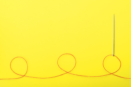 Red thread and needle on yellow background,  symbol of handmade and needlework. Copyspace