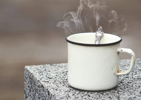 granite slab: Old mug with a hot drink on a granite slab in the outdoors. Photo in vintage color image style. Coffee break outdoors.